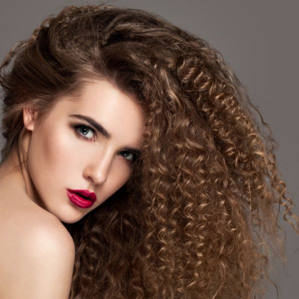 Beauty young woman with curly big and long hair. Permed hair.